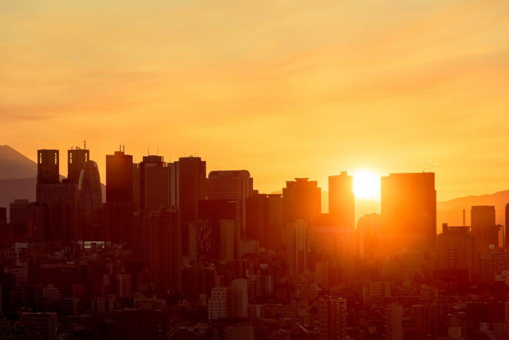 ビル群の隙間から陽が落ちる東京の夕暮れ